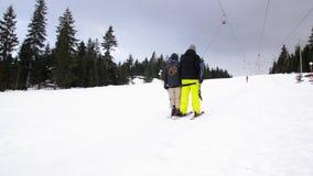 Esquiadores que usan el ancla del remonte en la montaña Gente que mueve lentamente ascendente en la elevación de la fricción e almacen de metraje de vídeo