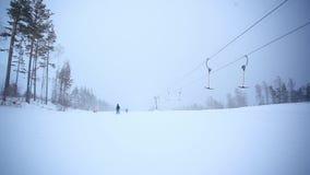 Esquiadores que vão abaixo da inclinação perto do elevador de esqui dentro vídeos de arquivo