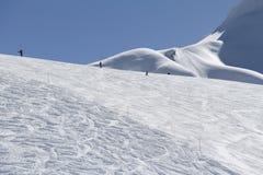 Esquiadores que van abajo de la cuesta en la estación de esquí Imágenes de archivo libres de regalías