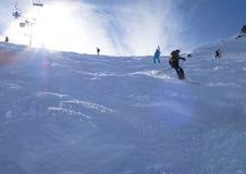 Esquiadores retroiluminados en nieve del polvo imagenes de archivo