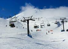 Esquiadores, snowboarders e turista viajando em uns teleféricos em uma montanha enevoada coberto de neve fotografia de stock