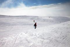 Esquiadores y snowboarders cuesta abajo en cuesta de la nieve Imagenes de archivo