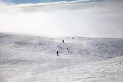 Esquiadores y snowboarders cuesta abajo en el cielo nevoso de la cuesta y de la luz del sol Fotografía de archivo libre de regalías