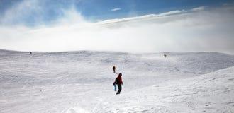 Esquiadores y snowboarders cuesta abajo en cuesta nevosa Imagen de archivo