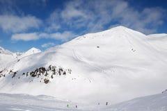Esquiadores y snowboarders cuesta abajo en rastro y las montañas con clo Foto de archivo libre de regalías