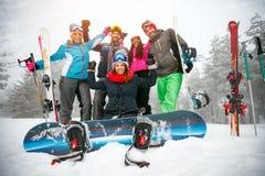Esquiadores y snowboarders de los amigos que se divierten en el invierno sitiado por la nieve f Fotos de archivo libres de regalías