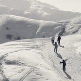 Esquiadores y snowboarders en el camino de la nieve en la mañana del invierno del sol Imagen de archivo