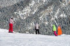 Esquiadores y snowboarders en la cuesta foto de archivo