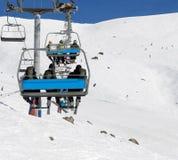 Esquiadores y snowboarders en la telesilla Imagen de archivo libre de regalías