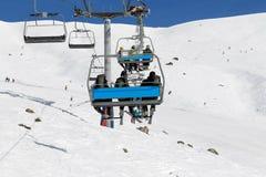 Esquiadores y snowboarders en la telesilla Foto de archivo libre de regalías