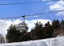 Esquiadores y snowboarders en la telesilla en montaña del invierno Fotografía de archivo