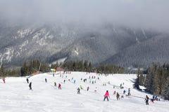 Esquiadores y snowboarders que gozan de buena nieve Fotografía de archivo libre de regalías