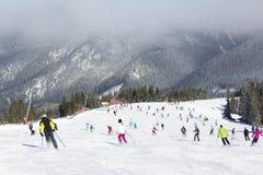 Esquiadores y snowboarders que gozan de buena nieve Foto de archivo libre de regalías