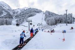 Esquiadores y snowboarders que montan en un travolator imagenes de archivo