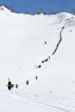 Esquiadores y snowboarders que suben la montaña escarpada para el freeride Imágenes de archivo libres de regalías
