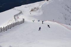 Esquiadores y snowboarders que van abajo de la cuesta Fotografía de archivo