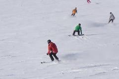 Esquiadores y snowboarders que van abajo de la cuesta Foto de archivo libre de regalías