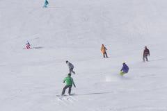 Esquiadores y snowboarders que van abajo de la cuesta Fotos de archivo libres de regalías