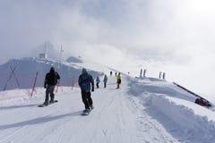 Esquiadores y snowboarders que van abajo de la cuesta Imagen de archivo