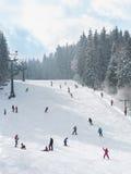 Esquiadores y snowboarders que van abajo de la cuesta Imagen de archivo libre de regalías