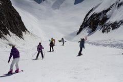 Esquiadores y snowboarders que van abajo de la cuesta en Fotos de archivo