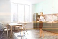 Esquina blanca de la cocina, encimeras verdes, mujer foto de archivo