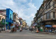 Esquina da rua típica da cidade em Phnom Penh em um dia em parte nebuloso Imagens de Stock Royalty Free