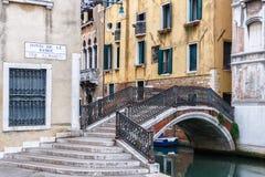 A esquina da rua Venetian amarela com um arco cercou a ponte Foto de Stock