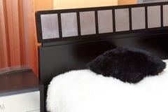 Esquina de la cama con la cubierta blanca de la manta de la piel Imagenes de archivo