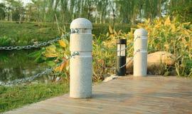 Esquina de la cubierta de madera con las barreras de piedra por el río Imágenes de archivo libres de regalías
