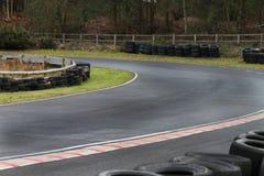Esquina de la pista que compite con del motor con la pared del neumático Fotos de archivo libres de regalías