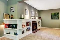 Esquina de la sala de estar con la chimenea y los estantes adornados Fotografía de archivo libre de regalías