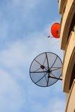 Esquina de las antenas parabólicas, negra y roja. Foto de archivo libre de regalías