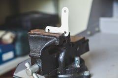 Esquina de metal con los agujeros atrapados en tornillo del banco Imagenes de archivo