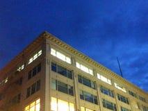Esquina del edificio de oficinas americano típico con los cielos nocturnos de oscurecimiento Foto de archivo libre de regalías