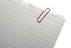 Esquina del papel de nota en blanco con el paper-clip rojo. Foto de archivo