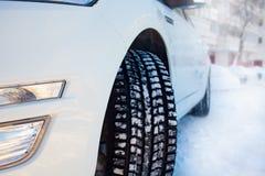 Esquina delantera del coche, neumático del invierno y el paisaje nevoso de la ciudad en Rusia fotografía de archivo