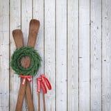 Esquis de madeira velhos na parede de madeira das pranchas com festão e a fita vermelha, fundo do inverno Foto de Stock Royalty Free