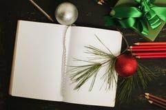 Esquissez le livre, la décoration de Noël et les crayons de couleur Image stock