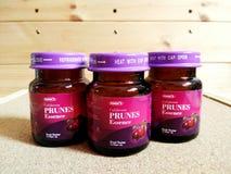 Essência das ameixas secas em umas garrafas etiquetadas fotografia de stock