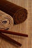 Ess-Stäbchen- und Bambusmatte stockbild