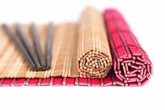 Ess-Stäbchen- und Bambusmatten für asiatische Nahrung Lizenzfreie Stockbilder