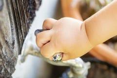 Essai d'enfant pour arrêter le robinet d'eau dans l'extérieur image libre de droits