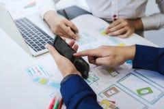 Essai de deux programmeurs codant des technologies avec le téléphone portable pour comparer le site Web mobile et de bureau Conce photo libre de droits
