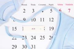 Essai de grossesse avec le résultat positif et habillement pour le mensonge nouveau-né sur le calendrier, prévoyant pour le bébé Photos stock