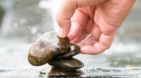 Essai de main de femmes pour placer les roches sur la ligne Photographie stock libre de droits