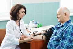 Essai de médecin de tension artérielle Photographie stock