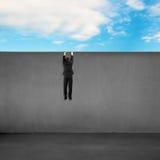 Essai de s'élever au-dessus du mur avec le fond de ciel bleu photos libres de droits
