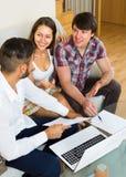 Essai de vendeur pour signer le contrat avec des couples Image stock