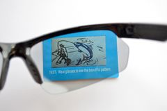 Essai des lunettes de soleil d'un sport avec l'effet photochromique sur l'image de essai bleue avec le pêcheur photographie stock libre de droits